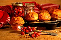 Delicious cranberry muffins with fresh berries on table