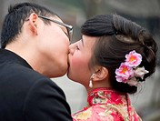 a young couple embracing and kissing on their wedding day