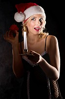 cute and attractive young woman with nightgown and a christmas hat shaking a little gift