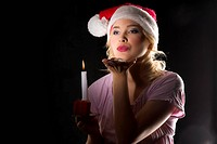 cute and attractive young woman with nightgown ant a christmas hat looking in the dark with a candle