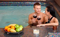 Young couple enjoying relaxation in spa with glass of wine.