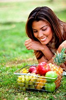 Healthy eating woman with a basket of fruits – outdoors