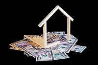 Simple wooden house symbol sitting on a pile of cash. Conceptual image for home loan, construction loan, general construction, etc. Isolated on a blac...