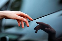 Human hand pointing to reflective surface, resembling Michelangelo´s painting ´Creation´. Shallow DOF, focus on finger.