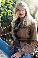 beautiful blond in a outside shot wearing winter dress and jacket with fur