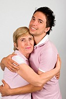 Portrait of mother and adult son hugging and smiling together and wearing pink tshirts,they are really family,over gray background