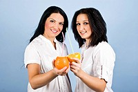 Two young woman holding fresh citrus fruits,orange and mandarin and drinking from a straw on blue background