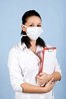 Young woman doctor wearing protective mask and holding clipboard on blue background