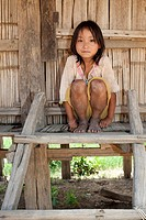 Asian girl Akha before timber house, ethnic group in Laos