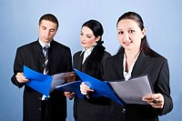 Business people reading folders with contracts ,focus on young businesswoman smiling for you