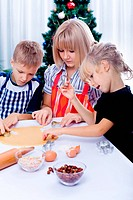 children preparing xmas cookies in front of christmas tree