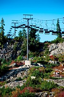 Ski Lift on rocky terrain in fall with red, green and orange plants