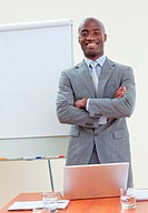 Confident ethnic businessman in office with folded arms smiling at the camera