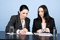 Two businesswomen having a meeting in office and one of them writing on papers and the other reading