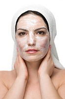 Woman at spa with a white towel on head and cream facial mask isolated on white background