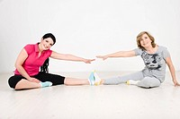 Active happy two women ,young and older training together on wooden floor