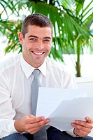 Smiling businessman reading some documents on sofa in workplace