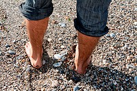 pair of men´s feet on the beach with pebbles