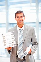 Happy young business man holding a building model with its blueprints