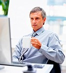 Mature business man drinking a cup of coffee while looking at the computer