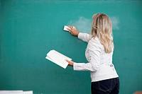 Female professor erases a chalkboard.