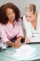 Two beautiful young businesswomen or lawyers, one African American one caucasian, discussing and signing a contract or legal document