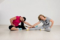 Active two women doing some exercises of gymnastic on wooden floor