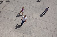 A group of people are walking away from each other on concrete squares.