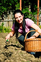 Happy young gardener woman working in garden at countryside