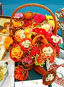 Basket full of artifically flowers made of crepe paper