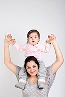 Mother holding her baby girl on her shoulders and smiling,copy space for text message