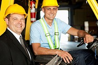 Manager and a forklift driver smiling at the camera.