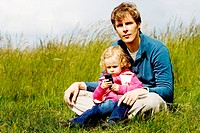 Father and child exploring mobile phone sitting in the grass