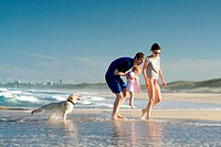 Young family with daughter and dog on the beach