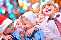 group of happy kids with Santa hats against lights background