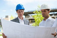 Two businessmen look through blueprints at a construction site.