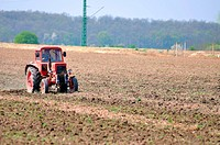 Red tractor on a field in early spring preparing the land for the new crops