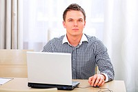 Closeup of serious young businessman using laptop