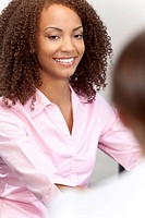 A beautiful mixed race African American young woman with perfect teeth and smile sitting and talking to a colleague out of focus in the foreground.