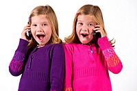 Beautiful twin sisters talk on their cell phones