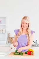 Gorgeous blonde female cutting vegetables in modern kitchen interior in her appartment