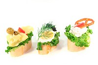 Canape with lettuce, cheese, sausage, cream cheese and eggs on a white background