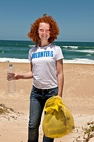 Young female volunteer collecting garbage on beach