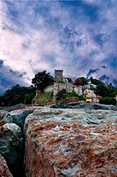 Scenic view of San Terenzo castle under cloudscape with boulders in foreground, Lerici, Italy.
