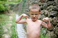 boy with angry face showing muscles without T-shirt, Ludiente, Castellón, Spain