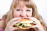 The young hungry woman bites the big hamburger