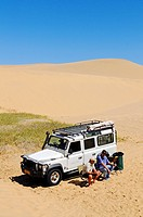 Two men sitting in front of a Landrover Defender off_road vehicle in the dunes of the Namib Naukluft National Park, part of the Namibian Skeleton Coas...