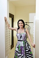 Portrait of a mid adult woman standing at doorway of dressing room in fashion boutique