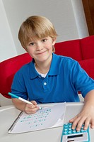 Portrait of little boy doing homework