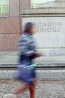 England, London, London Bridge. A woman walking past a stone plinth with London Bridge carved into it.